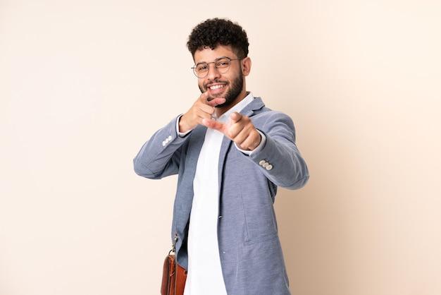 Jeune homme marocain d'affaires isolé sur un mur beige pointant vers l'avant et souriant