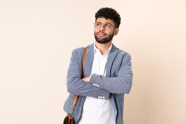 Jeune homme marocain d'affaires isolé sur un mur beige regardant en souriant