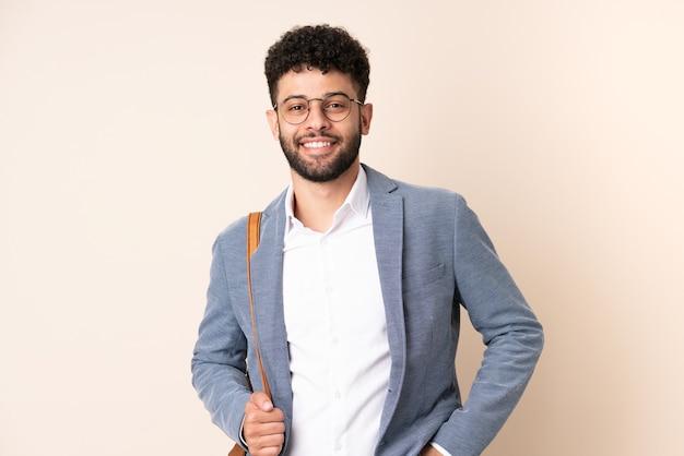 Jeune homme marocain d'affaires isolé sur mur beige en riant