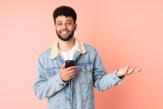 Jeune homme marocain à l'aide de téléphone mobile isolé sur mur rose étendant les mains sur le côté pour inviter à venir