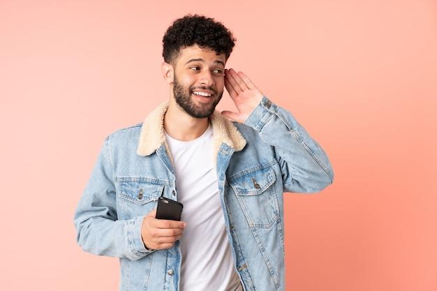 Jeune homme marocain à l'aide de téléphone mobile isolé sur rose écouter quelque chose en mettant la main sur l'oreille