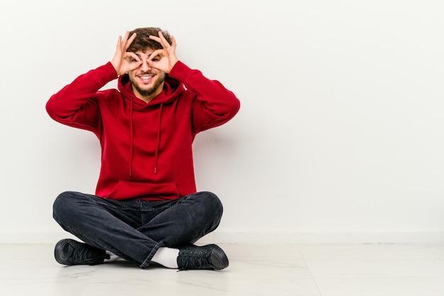 Jeune homme marocain assis sur le sol isolé sur blanc montrant signe correct sur les yeux