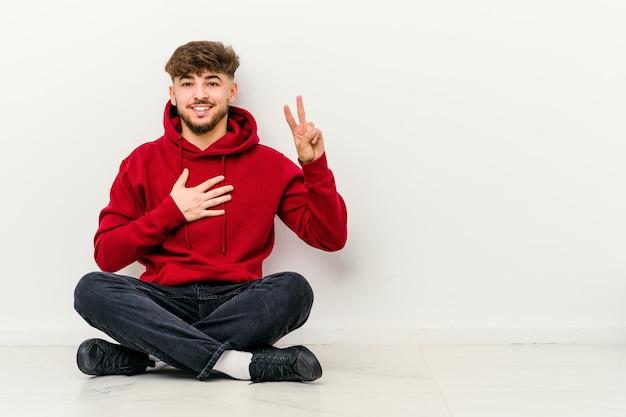 Jeune homme marocain assis sur le sol isolé sur blanc en prêtant serment, mettant la main sur la poitrine.