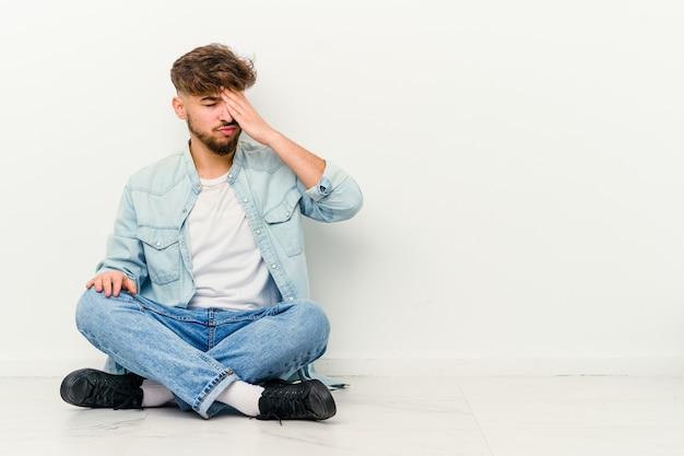 Jeune homme marocain assis sur le sol isolé sur un mur blanc ayant mal à la tête, touchant l'avant du visage.