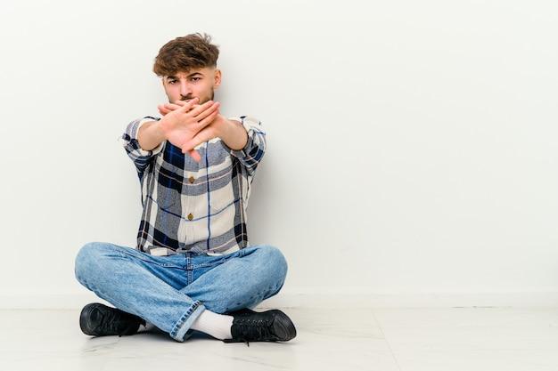 Jeune homme marocain assis sur le sol isolé sur un mur blanc debout avec la main tendue montrant un panneau d'arrêt, vous empêchant.