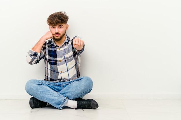 Jeune homme marocain assis sur le sol isolé sur un mur blanc jetant un coup de poing, la colère, les combats en raison d'une dispute, la boxe.