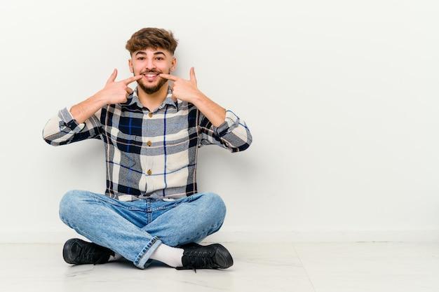 Jeune homme marocain assis sur le sol isolé sur des sourires blancs, pointant du doigt la bouche.