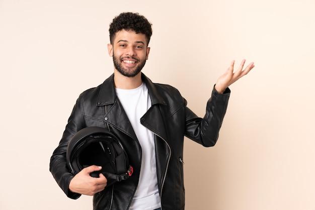 Jeune homme marocain avec un casque de moto isolé sur mur beige étendant les mains sur le côté pour inviter à venir