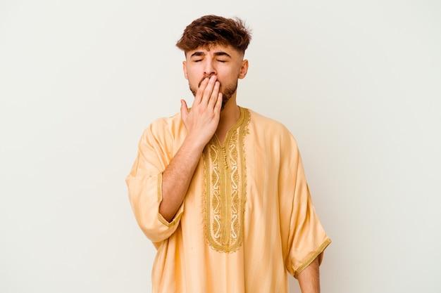 Jeune homme marocain isolé sur blanc le bâillement montrant un geste fatigué couvrant la bouche avec la main.