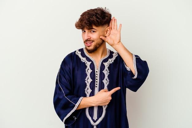 Jeune homme marocain isolé sur blanc essayant d'écouter un commérage.