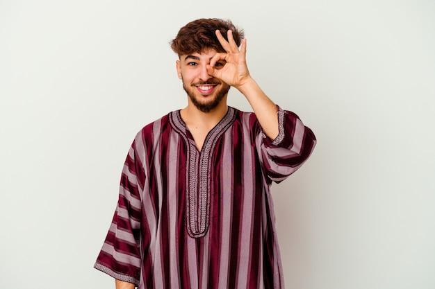 Jeune homme marocain isolé sur blanc excité en gardant le geste ok sur les yeux.