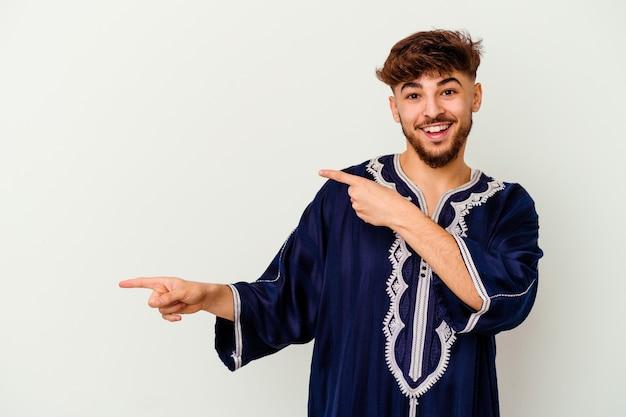 Jeune homme marocain isolé sur blanc excité pointant avec l'index loin.