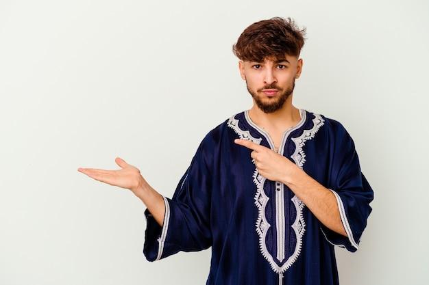 Jeune homme marocain isolé sur blanc excité tenant un espace de copie sur la paume.