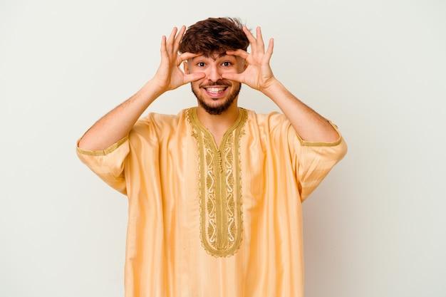 Jeune homme marocain isolé sur blanc gardant les yeux ouverts pour trouver une opportunité de succès.