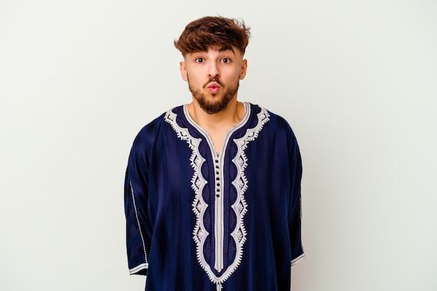 Jeune homme marocain isolé sur blanc hausse les épaules et les yeux ouverts confus.