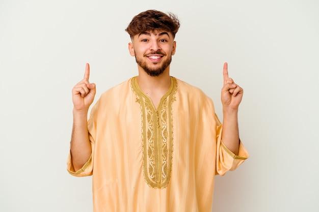 Jeune homme marocain isolé sur blanc indique avec les deux doigts avant montrant un espace vide.