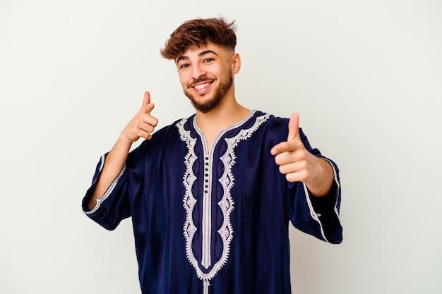 Jeune homme marocain isolé sur blanc pointant vers l'avant avec les doigts.