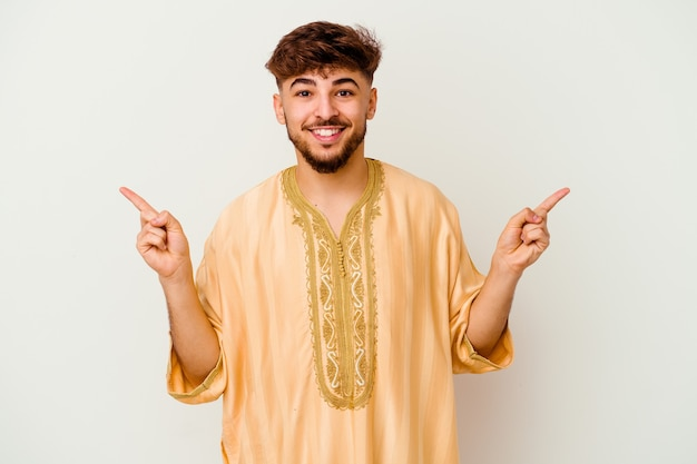 Jeune homme marocain isolé sur blanc pointant vers différents espaces de copie, en choisissant l'un d'entre eux, montrant avec le doigt.