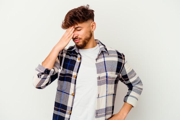 Jeune homme marocain isolé sur un mur blanc ayant mal à la tête, touchant l'avant du visage.