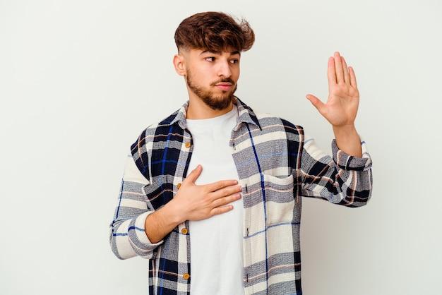 Jeune homme marocain isolé sur un mur blanc en prêtant serment, mettant la main sur la poitrine.