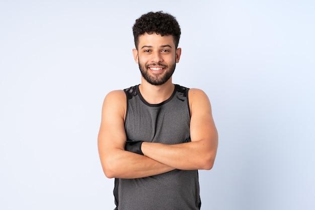 Jeune homme marocain isolé sur mur bleu avec les bras croisés