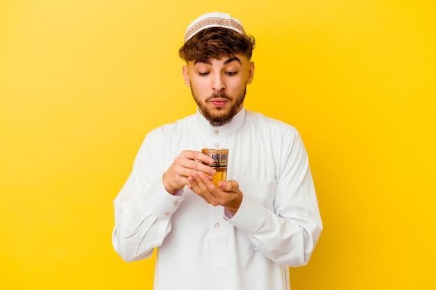 Jeune homme marocain portant le costume arabe typique de boire du thé isolé sur mur jaune