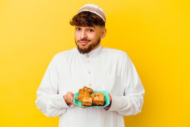 Jeune homme marocain portant le costume arabe typique de manger des bonbons arabes isolé sur mur jaune