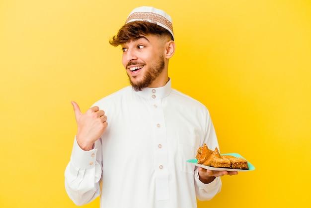 Jeune homme marocain portant le costume arabe typique de manger des bonbons arabes isolés sur fond jaune points avec le pouce, riant et insouciant.