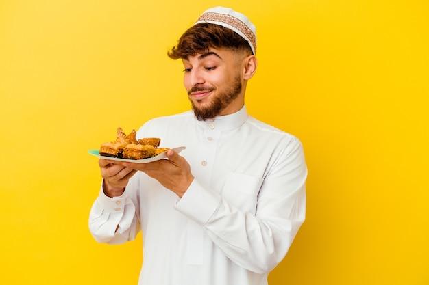 Jeune homme marocain portant le costume arabe typique de manger des bonbons arabes isolés sur jaune