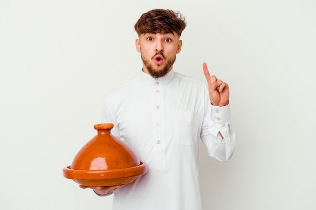 Jeune homme marocain portant le costume arabe typique tenant un tajine isolé sur blanc ayant une bonne idée