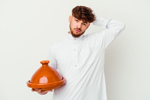 Jeune homme marocain portant le costume arabe typique tenant un tajine isolé sur blanc choqué, s'est souvenu d'une réunion importante.