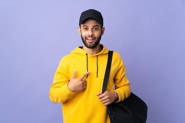 Jeune homme marocain sport avec sac de sport isolé sur violet avec expression faciale surprise