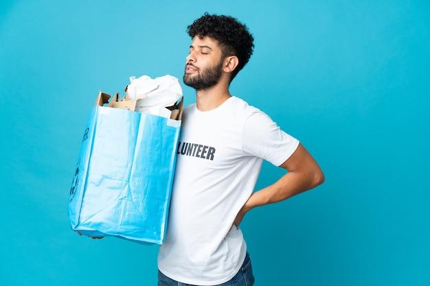 Jeune homme marocain tenant un sac de recyclage plein de papier à recycler sur isolé souffrant de maux de dos pour avoir fait un effort