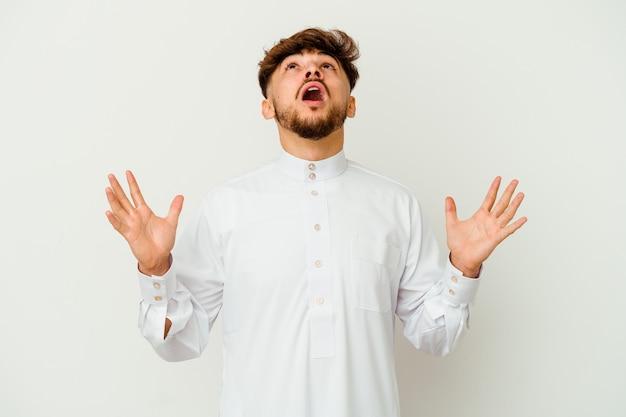 Jeune homme marocain vêtu d'un vêtement arabe typique isolé sur blanc criant vers le ciel, levant les yeux, frustré.