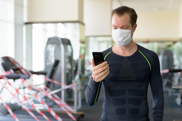 Jeune homme avec masque à l'aide d'un téléphone au gymnase pendant le coronavirus covid-19