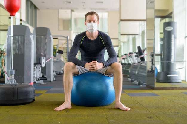 Jeune homme avec masque assis sur un ballon d'exercice au gymnase pendant le coronavirus covid-19
