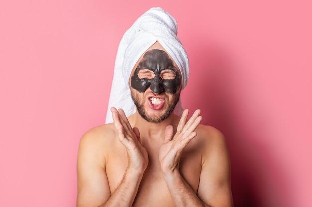 Jeune homme avec masque cosmétique aux yeux fermés sur fond rose