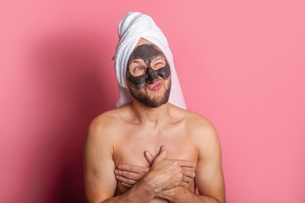 Jeune homme avec un masque cosmétique sur son visage, clins d'oeil pensivement avec un oeil sur un fond rose.