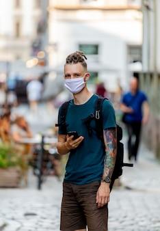 Jeune homme avec masque facial et dreadlocks utilise un téléphone mobile dans la rue