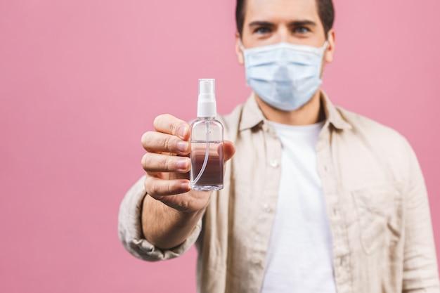 Jeune homme en masque facial stérile isolé sur mur rose. coronavirus pandémique épidémique 2019-ncov sars covid-19 virus virus concept. bouteille avec un désinfectant liquide antibactérien à base d'alcool.