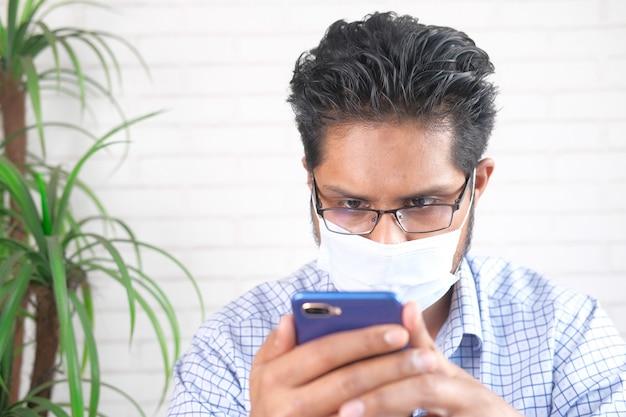 Jeune homme, à, masque facial, utilisation, téléphone intelligent, intérieur
