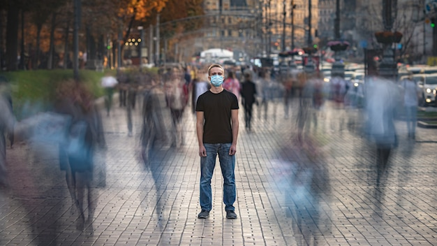 Le jeune homme avec un masque médical se tient dans la rue bondée