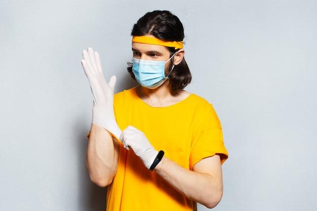Jeune homme avec masque médical sur le visage, met des gants chirurgicaux contre les virus. fond de mur gris. portant une chemise jaune et une bande.