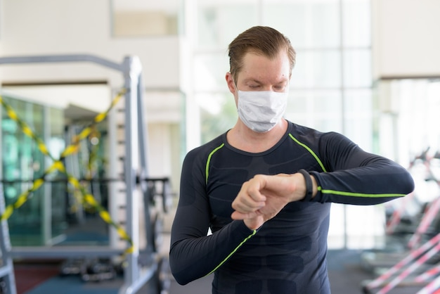 Jeune homme avec un masque pour se protéger contre l'épidémie de coronavirus vérifiant une smartwatch dans une salle de sport pendant le coronavirus covid-19