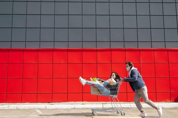 Jeune homme en masque poussant le chariot avec sa petite amie pendant qu'ils s'amusent pendant le coronavirus