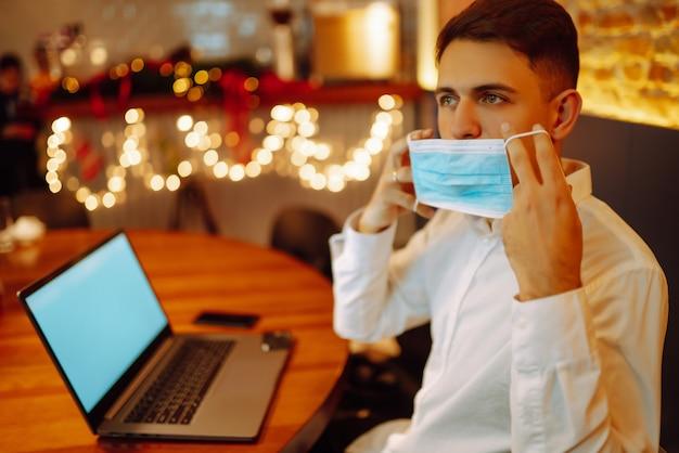 Jeune homme avec masque protecteur travaillant sur ordinateur portable à la maison pendant les vacances d'hiver.