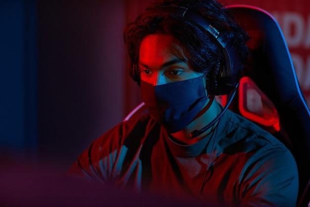 Jeune homme en masque de protection assis sur une chaise en face de l'ordinateur et travaillant dans un bureau sombre
