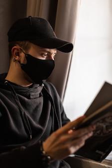 Jeune homme avec masque de protection médicale et casquette noire dans un magazine de lecture à capuche au café