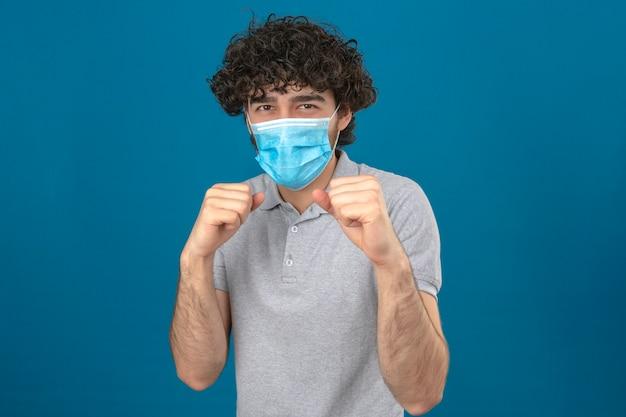 Jeune homme en masque de protection médicale debout dans la pose de boxeur avec le poing prêt à se battre sur fond bleu isolé
