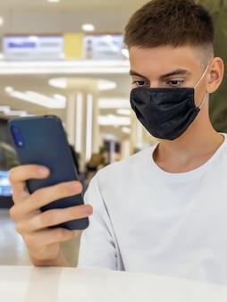 Jeune homme en masque de protection avec smartphone dans ses mains dans un centre commercial